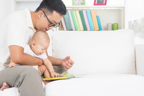 dad reading to newborn